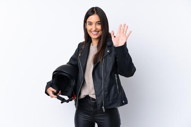 Молодая брюнетка с мотоциклетным шлемом на белом фоне Premium Фотографии