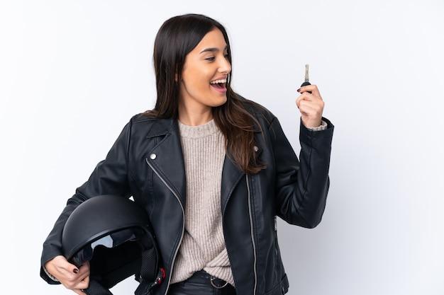 オートバイのヘルメットと分離の白い壁の上のキーを保持している若いブルネットの女性 Premium写真