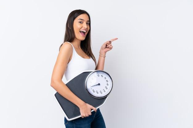 Молодая женщина брюнет над изолированной белой стеной с веся машиной Premium Фотографии