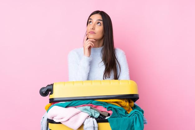 Путешественник женщина с чемоданом, полным одежды над розовой стеной, думая, идея Premium Фотографии