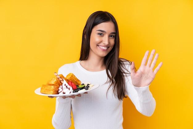 幸せな表情で手で敬礼分離壁にワッフルを置く若いブルネットの女性 Premium写真