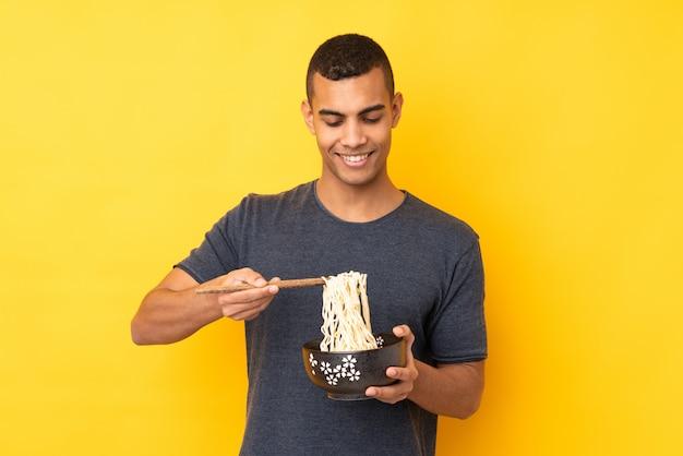 箸で麺のボウルを保持している孤立した黄色の壁の上の若いアフリカ系アメリカ人 Premium写真