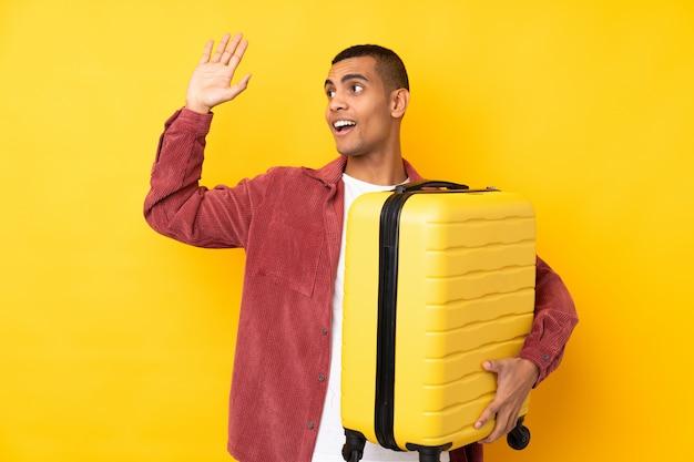 Молодой человек афроамериканца над изолированной желтой стеной в отпуске с чемоданом путешествия и салютов Premium Фотографии