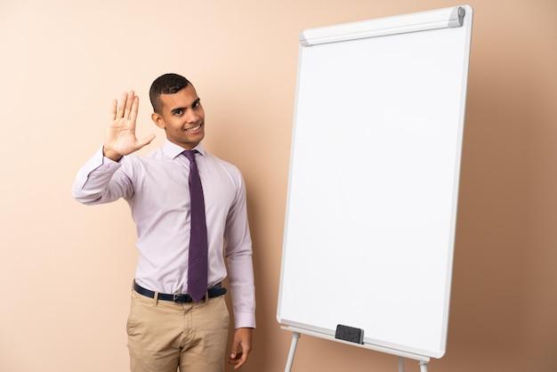 Молодой деловой человек на изолированной стене, давая представление на белой доске и салютов с рукой Premium Фотографии