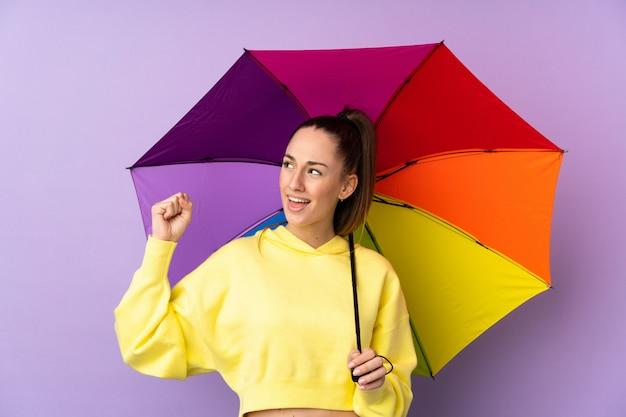 勝利を祝う孤立した紫色の壁に傘を置く若いブルネットの女性 Premium写真