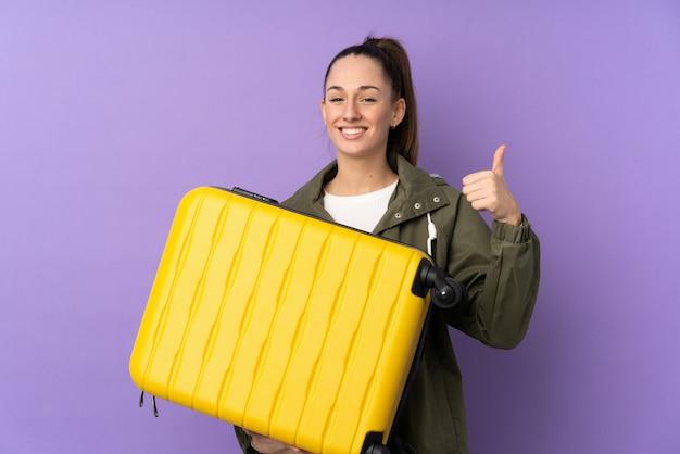 旅行スーツケースと親指アップと休暇で孤立した紫色の壁の上の若いブルネットの女性 Premium写真