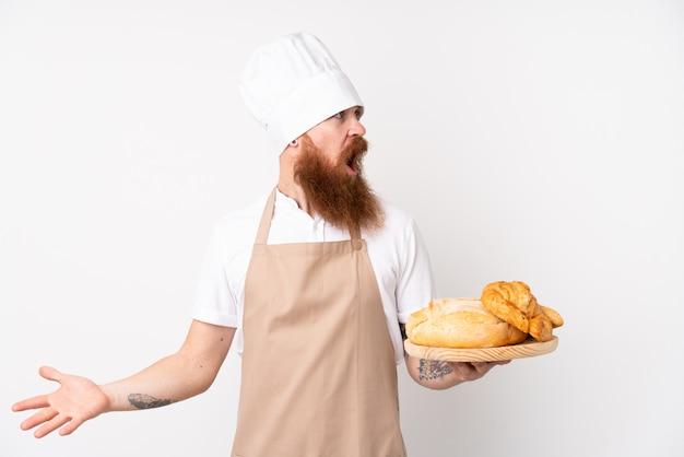 シェフの制服を着た赤毛の男。驚きの表情でいくつかのパンのテーブルを保持している男性のパン屋 Premium写真