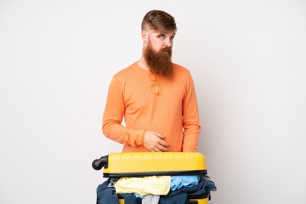 Человек путешественника с чемоданом, полным одежды над изолированной белой стеной, стоящей и смотрящей в сторону Premium Фотографии