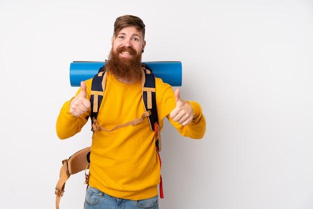Молодой человек альпиниста с большим рюкзаком над изолированной белой стеной, давая недурно жест Premium Фотографии