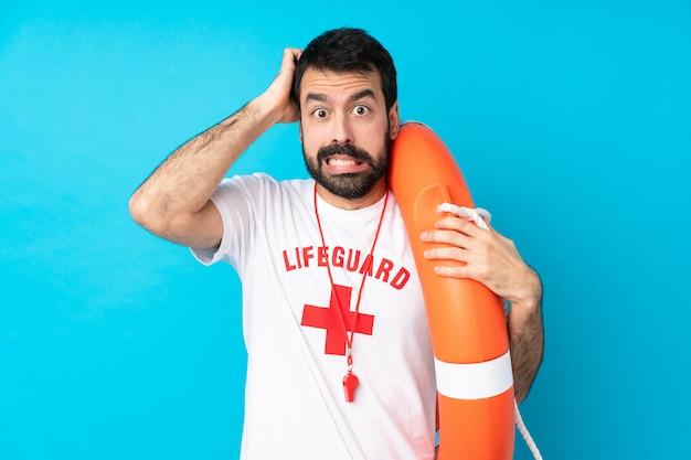 Спасатель человек над изолированной синей стеной расстроен и берет руки на голову Premium Фотографии