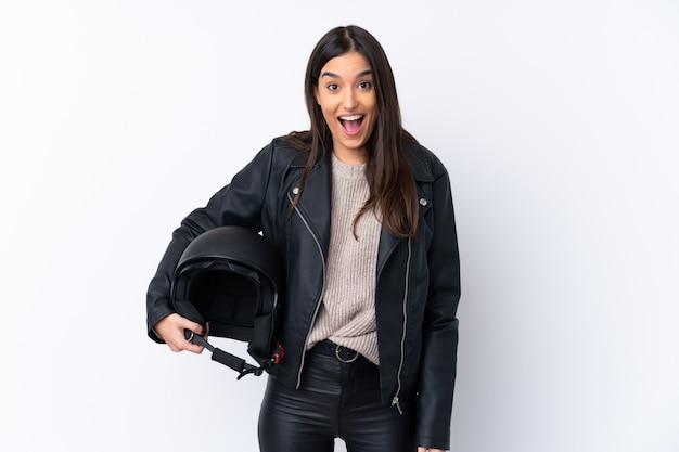 驚きとショックを受けた表情で孤立した白い壁にオートバイのヘルメットを持つ若いブルネットの女性 Premium写真