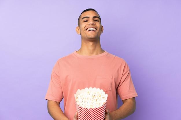 ポップコーンの大きなバケツを保持している孤立した青い壁の上の若いアフリカ系アメリカ人 Premium写真