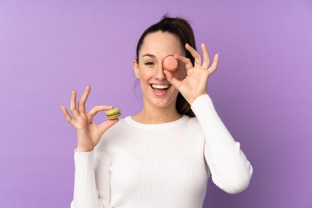 カラフルなフランスのマカロンを保持している孤立した紫色の壁の上の若いブルネットの女性 Premium写真