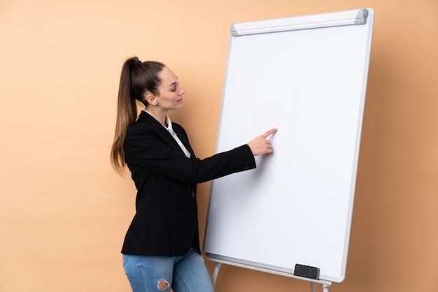 Молодая бизнес-леди над изолированной стеной давая представление на белой доске и писать в нем Premium Фотографии