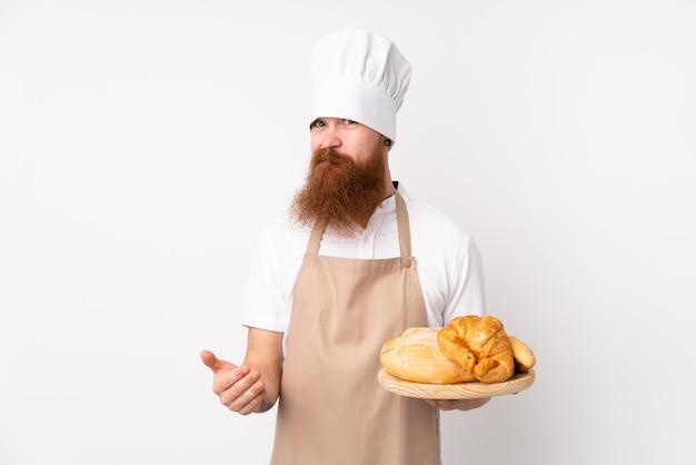 Рыжий мужчина в форме шеф-повара. мужской пекарь держит стол с несколькими хлебами, делая сомнение жест, поднимая плечи Premium Фотографии