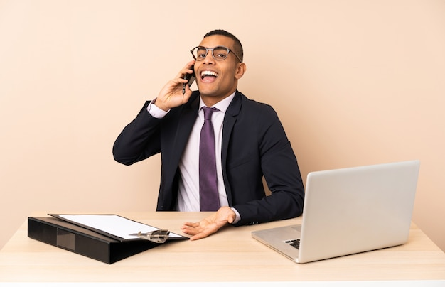 ノートパソコンと他のドキュメントと彼のオフィスで誰かと携帯電話で会話を続ける若いビジネスマン Premium写真