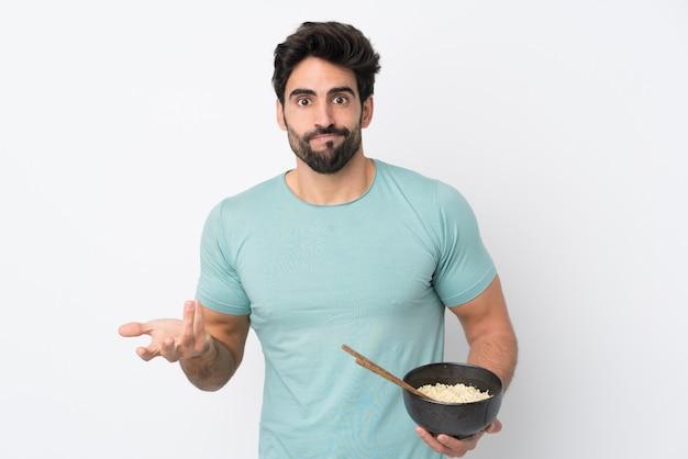 Молодой красавец с бородой над изолированной белой стеной, делая сомнения сомнения, поднимая плечи, держа миску лапши с палочками для еды Premium Фотографии