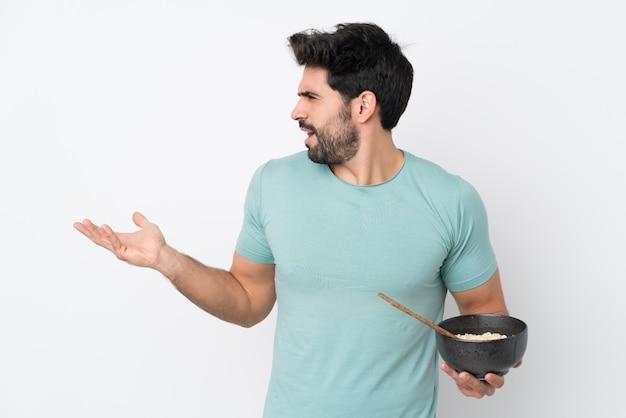 Молодой красавец с бородой на изолированной белой стене с удивленным выражением лица, держа миску лапши с палочками для еды Premium Фотографии