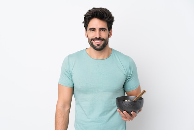 Молодой красивый мужчина с бородой над изолированной белой стеной, много улыбаясь, держа миску лапши с палочками для еды Premium Фотографии