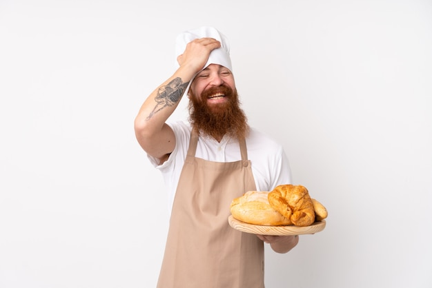 Рыжий мужчина в форме шеф-повара. мужской пекарь, держащий стол с несколькими хлебами, кое-что понял и намереваясь найти решение Premium Фотографии