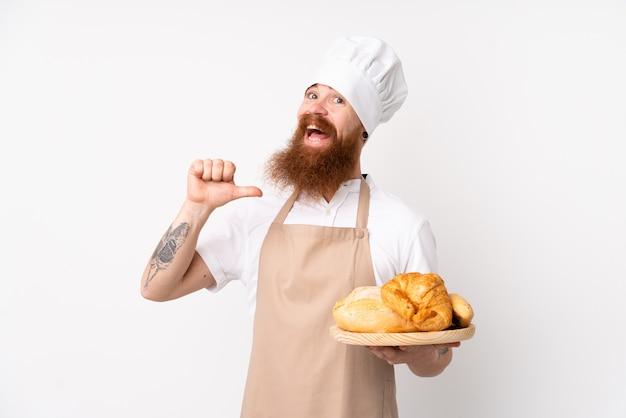 Рыжий мужчина в форме шеф-повара. мужской пекарь держит стол с несколькими хлебами гордый и самодовольный Premium Фотографии