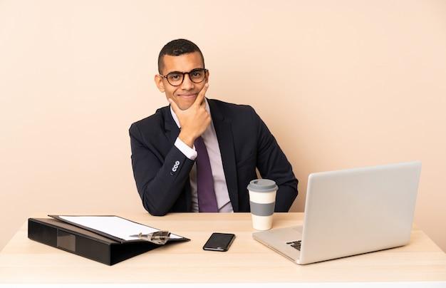 ノートパソコンと他のドキュメントを笑顔で彼のオフィスで若いビジネスマン Premium写真