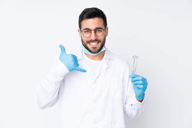 Стоматолог мужчина держит инструменты, изолированные на белой стене, делая жест телефона Premium Фотографии