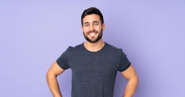 腰に腕でポーズと分離の紫色の壁に笑みを浮かべて白人のハンサムな男 Premium写真