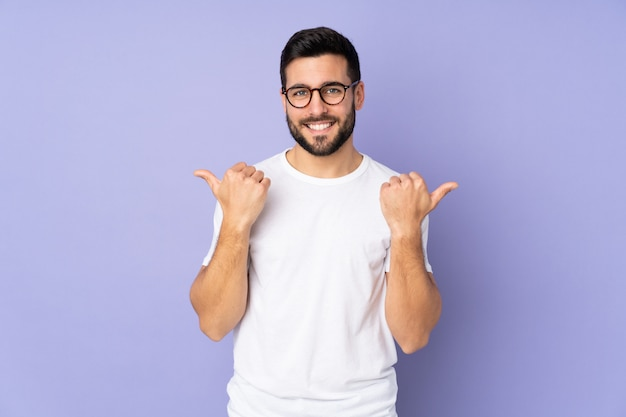 Кавказский красавец над изолированной стеной с недурно жест и улыбается Premium Фотографии