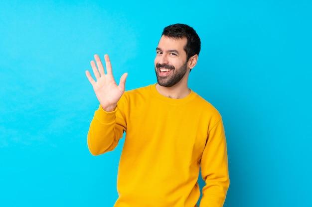 幸せな表情で手で敬礼分離の青い壁の上の若い白人男 Premium写真