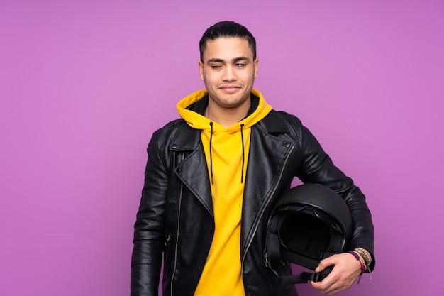 Человек с мотоциклетным шлемом, изолированный на фиолетовой стене, стоит и смотрит в сторону Premium Фотографии
