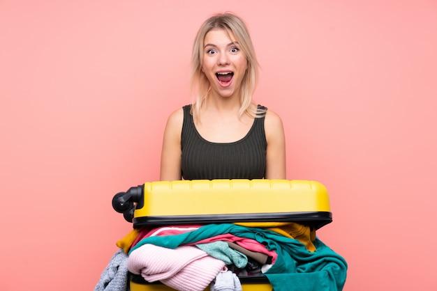 Путешественница с чемоданом, полным одежды, над розовой стеной с удивленным выражением лица Premium Фотографии