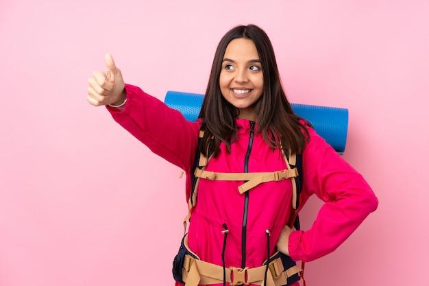 ジェスチャーを親指を与える分離のピンクの壁の上の大きなバックパックを持つ若い登山家女性 Premium写真