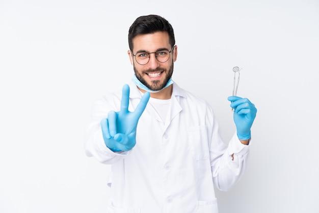 Человек дантиста держа инструменты изолированные на белой стене усмехаясь и показывая знак победы Premium Фотографии