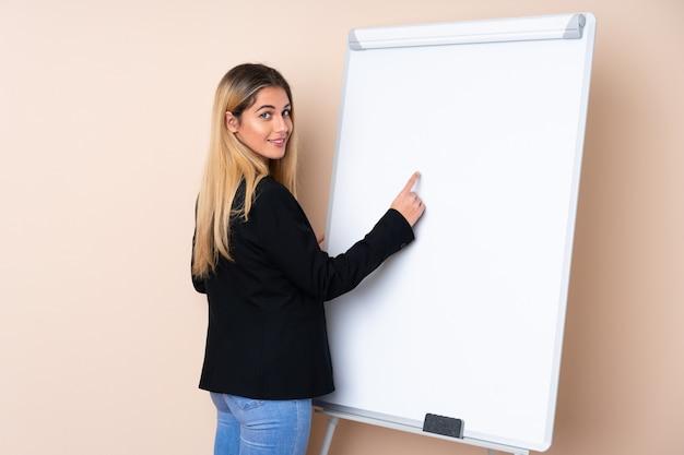 Молодая уругвайская женщина дает представление на белой доске и пишет в нем Premium Фотографии