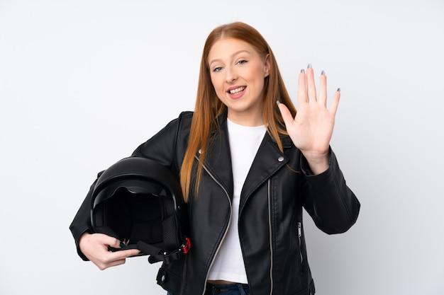 Рыжая молодая женщина с мотоциклетным шлемом на белом фоне Premium Фотографии