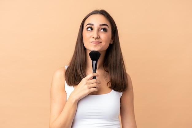 化粧ブラシを押しながら考えてベージュの若い女性 Premium写真