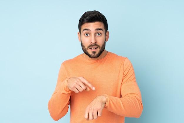 Кавказский красавец, делая жест опоздания над синей стеной Premium Фотографии