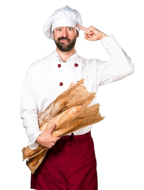 いくつかのパンを保持し、クレイジーなジェスチャーを作る若いパン屋 無料写真