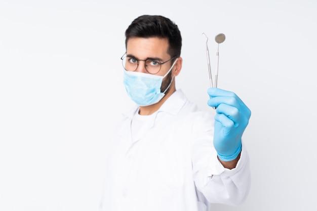 Стоматолог мужчина держит инструменты на белой стене Premium Фотографии