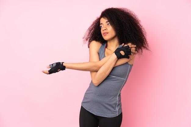 Молодая спортивная женщина на розовом растяжение руки Premium Фотографии