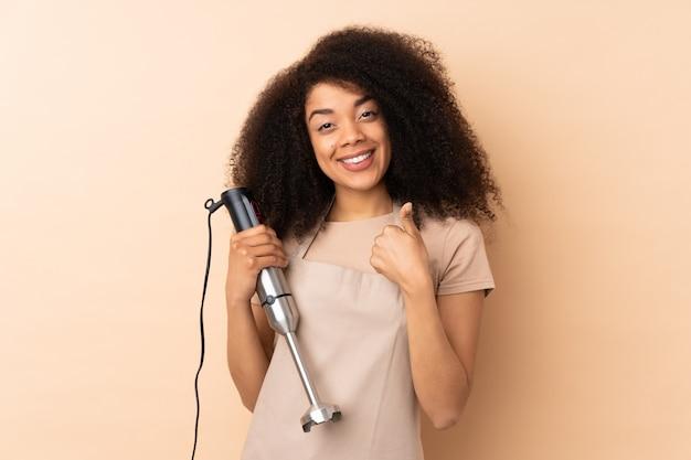 Молодая афро-американская женщина используя ручной блендер на бежевой стене давая жест больших пальцев руки вверх Premium Фотографии