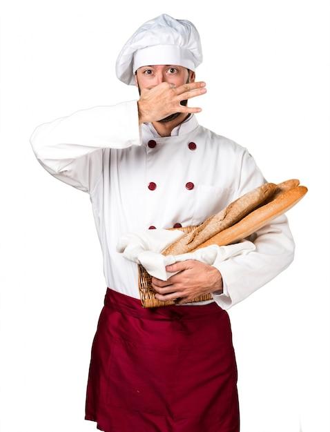いくつかのパンを保持している若いパン屋悪臭ジェスチャーを作る 無料写真