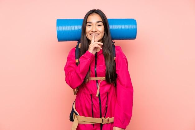 沈黙のジェスチャーをしているピンクの壁に大きなバックパックを持つ若い登山家インドの女の子 Premium写真