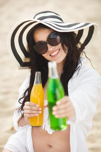 ビーチでカクテルを飲んでかなり若い女性。ドリンクを提供する魅力的な女の子。レモネードを飲む美しい女性 Premium写真