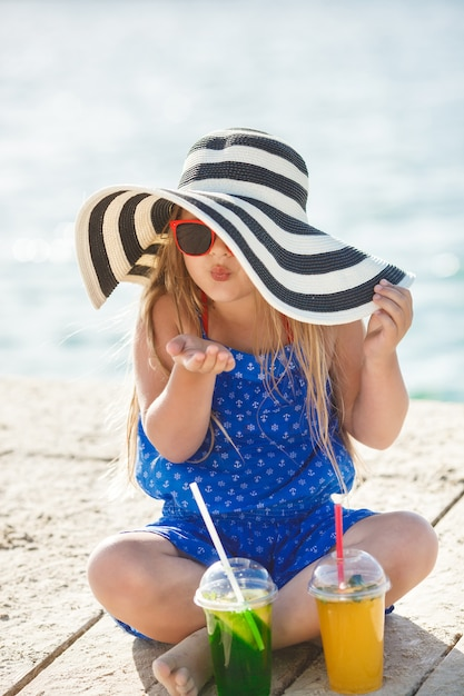 海の上のかわいい女の子。夏には帽子の少女。海岸線の愛らしい子。 Premium写真