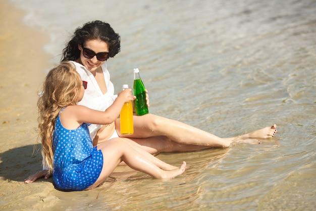 若い可愛い母と楽しんでビーチで彼女の小さな娘 Premium写真