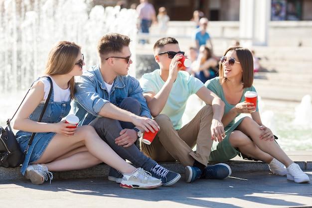 屋外で一緒に楽しんで若い魅力的な人々。コーヒーを飲みながら笑顔の人々。一緒に歩いている友人のグループ。 Premium写真
