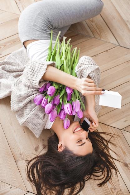 電話で話していると、花を持って陽気な若い女性。チューリップの美しい女性 Premium写真