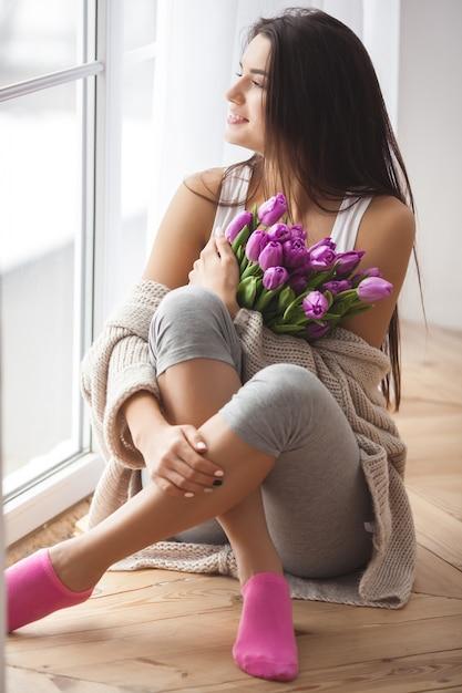 花を保持している若い魅力的な女性。ベッドの上に横たわるチューリップと美しい女性 Premium写真
